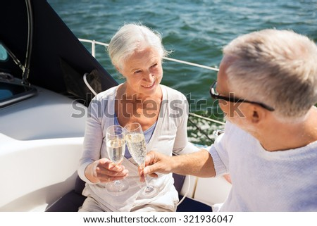 sailing, age, travel, holidays and people concept - happy senior couple clinking champagne glasses on sail boat or yacht deck floating in sea - stock photo