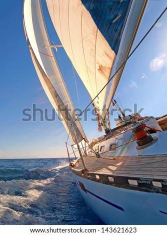 Sailing boat in blue open sea  - stock photo