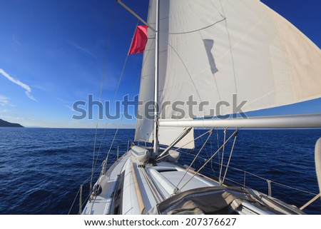 Sailing boat in the open blue sea  - stock photo