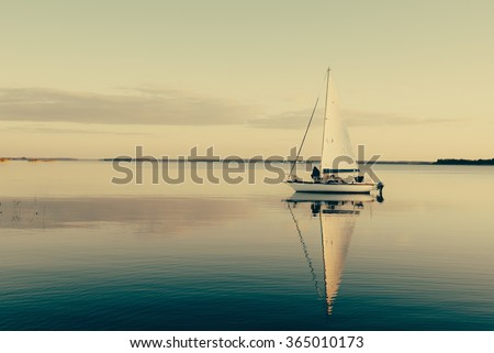 Sailing boat on a calm lake with reflection in the water. Serene scene landscape. Horizontal vintage effect photograph. - stock photo