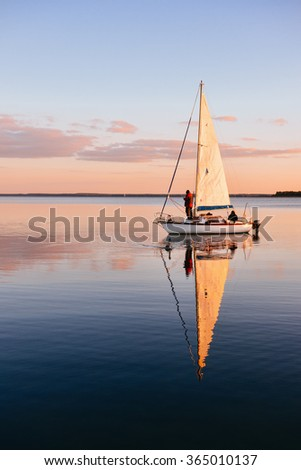 Sailing boat on a calm lake with reflection in the water. Serene scene landscape. Vertical photograph. - stock photo