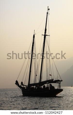 Sailing boat on lake Garda, Italy at dusk - stock photo