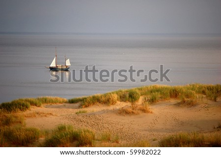 Sailing boat on still waters near dunes (with footprints) of shore, evening. Nida, Lithuania - stock photo