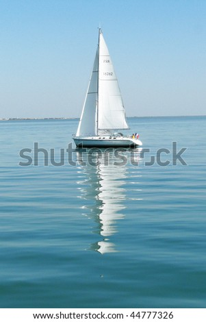 Sailing boat on the Atlantic ocean during a calm summer day - stock photo