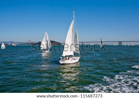 Sailing boat racing in San Francisco. San Francisco bridge at the background. - stock photo