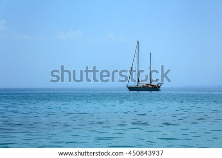 Sailing boat sitting calmly on the Mediterranean sea with clear skies and blue waters. - stock photo