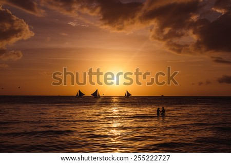 Sailing boats on the horizon and silhouette of lovely couple against a beautiful sunset on tropical exotic white beach on Boracay island, Philippines. - stock photo
