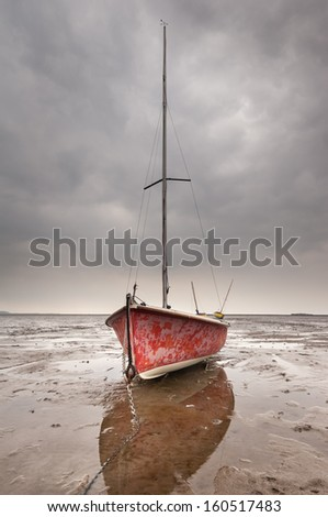 Sailing dinghies stranded on the mudflats of the Dee Estuary at Wirral Beach. Hilbre Island lies on the right horizon. - stock photo