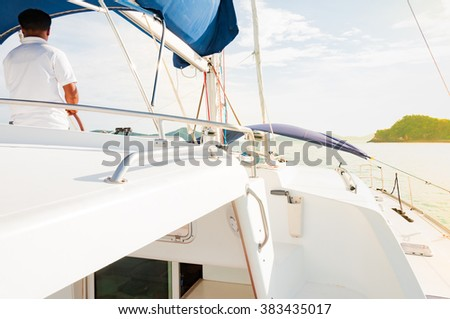Sailing luxury yacht during sunset by a man in Phuket, Thailand - stock photo