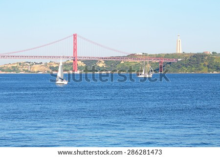 Sailing on the river Tejo with the 25 Abril bridge and the Christo Rei in Lisbon Portugal - stock photo