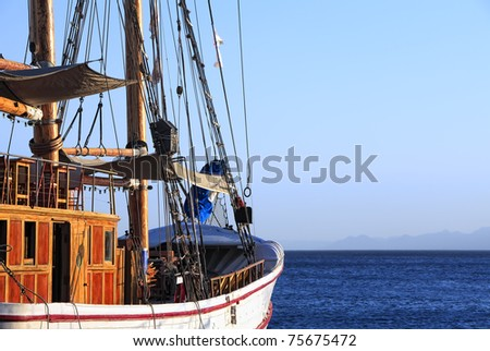 Sailing ship floating by sea and mountain in a fog before it - stock photo