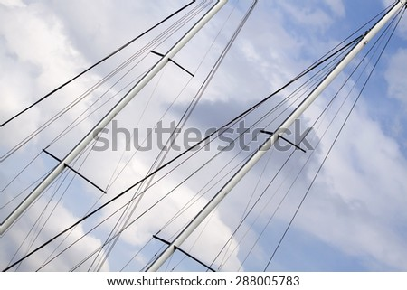Sailing ship mast details in the cloudy blue sky - stock photo