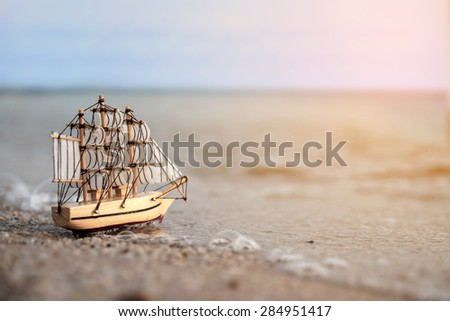 Sailing ship model on the beach  - stock photo