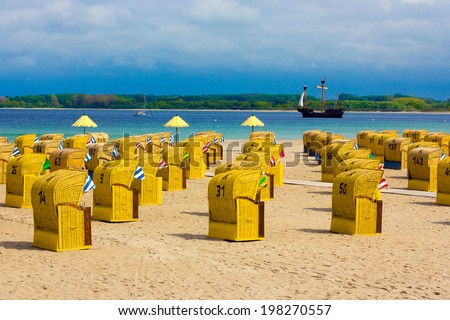 Sailing ship passing hooded beach chairs at Baltic Sea - stock photo
