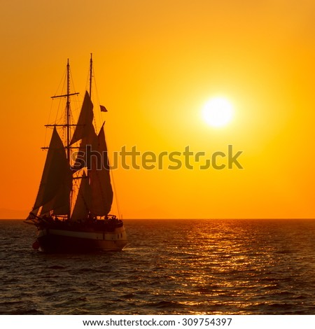 Sailing ship silhouette in red sunset on the sea - stock photo