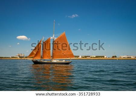 Sailing ship yachts with orange sails,Boston coast - stock photo