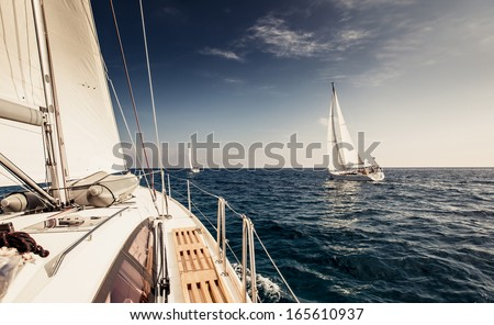 Sailing ship yachts with white sails in the open sea - stock photo