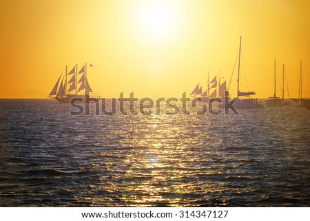 Sailing ships on the sea in red sunset - stock photo