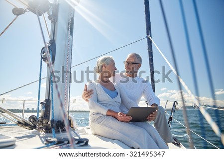 sailing, technology, tourism, travel and people concept - happy senior couple with tablet pc computer talking on sail boat or yacht deck floating in sea - stock photo