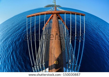 Sailing to a desert island, fish eye view from a bow of the yacht, island Kelifos between Sithonia and Kassandria, Chalkidiki, Greece - stock photo