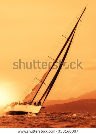 sailing yacht at sunset on the sea - stock photo