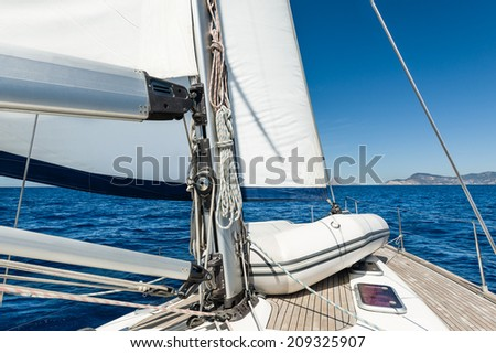 Sailing yacht going on her sails in calm weather with dinghy on board - stock photo