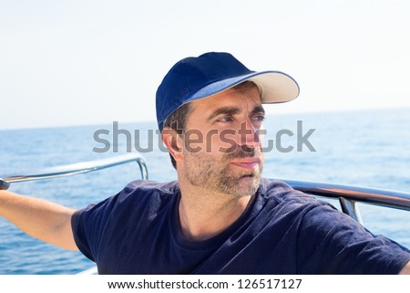 Sailor man at boat bow with cap looking away the sea while sailing - stock photo