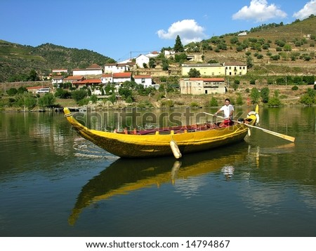 sailor rowing a traditional rebelo boat in the douro river current - stock photo
