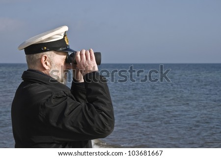 Sailor with binoculars observing the sea in calm weather - stock photo