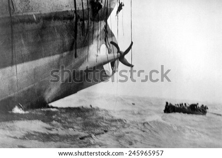 Sailors escape from vessel torpedoed by German submarine in WWI. Men can be seen sliding down ropes as a life boat leaves. Ca. 1917. - stock photo