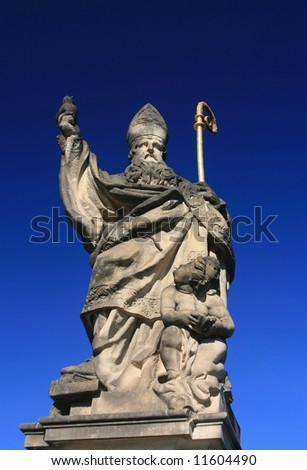Saint Augustine's statue –holding a burning heart in hand, Charles bridge in Prague,Czech Republic. - stock photo