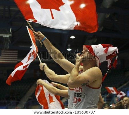 SAINT JOHN, CANADA - March 19: Team Canada fans wave Canadian flags at the Ford World Women's Curling Championship March 19, 2014 in Saint John, Canada. - stock photo