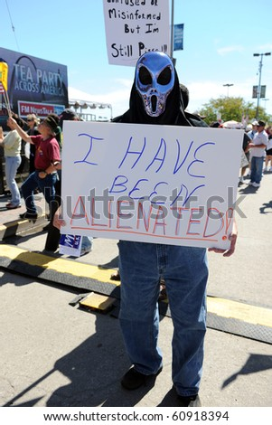 SAINT LOUIS, MISSOURI - SEPTEMBER 12: Man dressed in alien costume holding sign at rally of Tea Party Patriots in Downtown Saint Louis under the Arch, on September 12, 2010 in Saint Loius, Missouri - stock photo