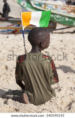SAINT LOUIS, SENEGAL, DECEMBER 17: Rear view of young African kid playing on the beach and holding the Senegalese flag. Saint Louis, Senegal 2013. - stock photo
