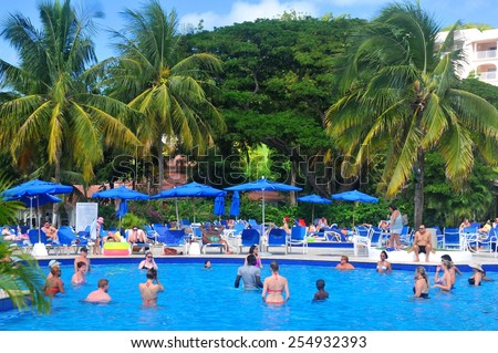 SAINT LUCIA, CARIBBEAN - DECEMBER 10, 2014: Tourists exercise in the swimming pool in exotic resort in Saint Lucia, Caribbean - stock photo