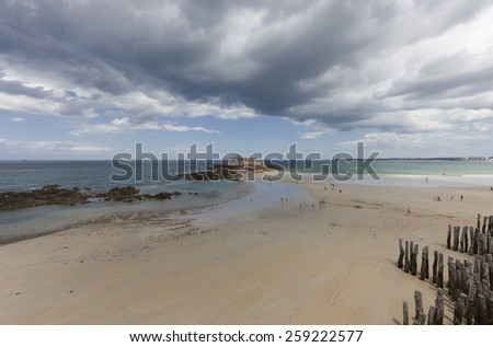 SAINT-MALO, FRANCE - JULY 6, 2011: People enjoying the beach in front of the tidal island Petit Be in Saint-Malo. The fort was built in the 17th century and designed by Vauban. - stock photo