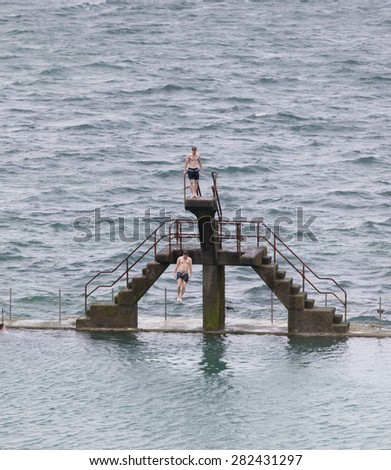 SAINT-MALO, FRANCE - JULY 6, 2011: Young man jumping into seawater pool. Another man is waiting on the diving platform. - stock photo