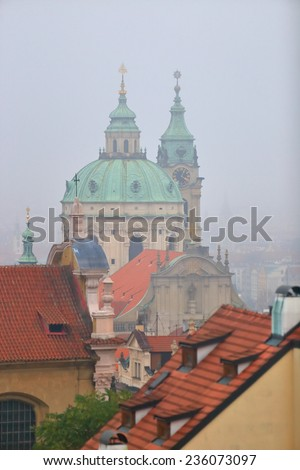 Saint Nicholas Church (Cathedral) surrounded by roof tops in foggy weather, Prague, Czech Republic - stock photo