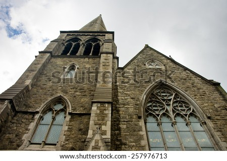 Saint Patrick cathedral detail of building and window in cloudy day, view from the ground. Dublin, Ireland - stock photo