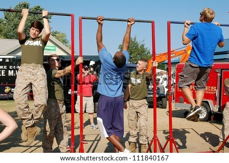 SAINT PAUL, MINNESOTA- SEPTEMBER 2:  Unidentified members of the US Marines test fair-goers for fitness at the Minnesota State Fair on September 2, 2012, in St. Paul, Minnesota.  Attendance has averaged 142.000 per day at the fair. - stock photo