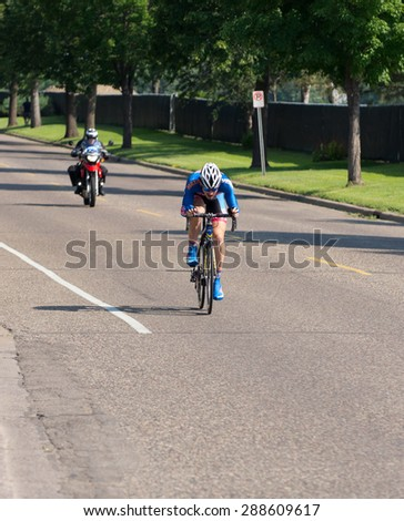 SAINT PAUL, MN/USA - JUNE 17, 2015: Pro cyclist Chris Barton races toward finish of Stage One time trial at the prestigious North Star Grand Prix pro cycling event in Saint Paul - stock photo