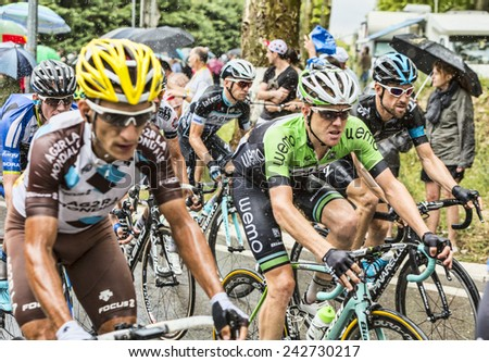 SAINT REMY DE PROVENCE, FRANCE - JUL 20:The peloton rides on a wet slippery road curve in Saint Remy de Provence during the stage 15 of Le Tour de France on July 20 2014 - stock photo
