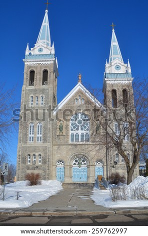 Saint-Romuald church building with a bell tower and clock tower; Farnham Quebec Canada - stock photo