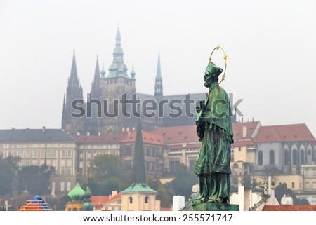 Saint statue decorates the Charles bridge and Prague castle in the background, Prague, Czech Republic - stock photo