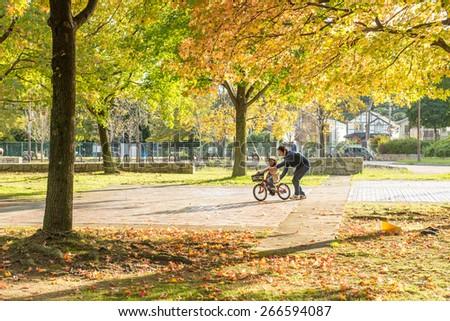 SAKAI, JAPAN - NOVEMBER 3, 2014: Father teaching son to ride bike.  - stock photo