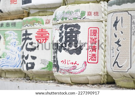 Sake Casks - Barrels of Japanese rice wine lined and stacked at the entrance of a Shrine. - stock photo