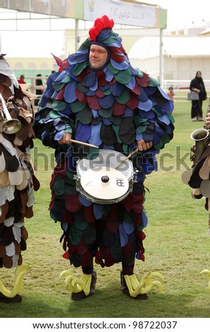 SAKHIR, BAHRAIN - MARCH 23: A Orchestra dressed up as hens performs on March 23, 2012 in Bahrain International Endurance Village, Sakhir during the Bahrain Animal Production Show 2012 - stock photo