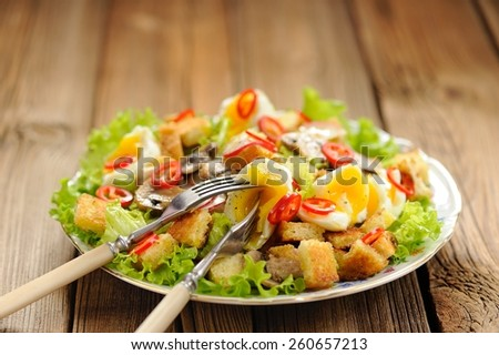 Salad Caesar with mushrooms, eggs, chili and radish with two forks on wooden background selective focus with space - stock photo