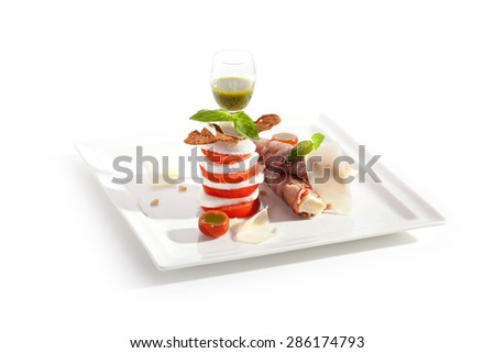 Salad Caprese with Bacon Wrapped Bread and Pesto Sauce - stock photo