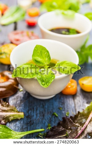 Salad dressing and oil with basil leaves, close up - stock photo